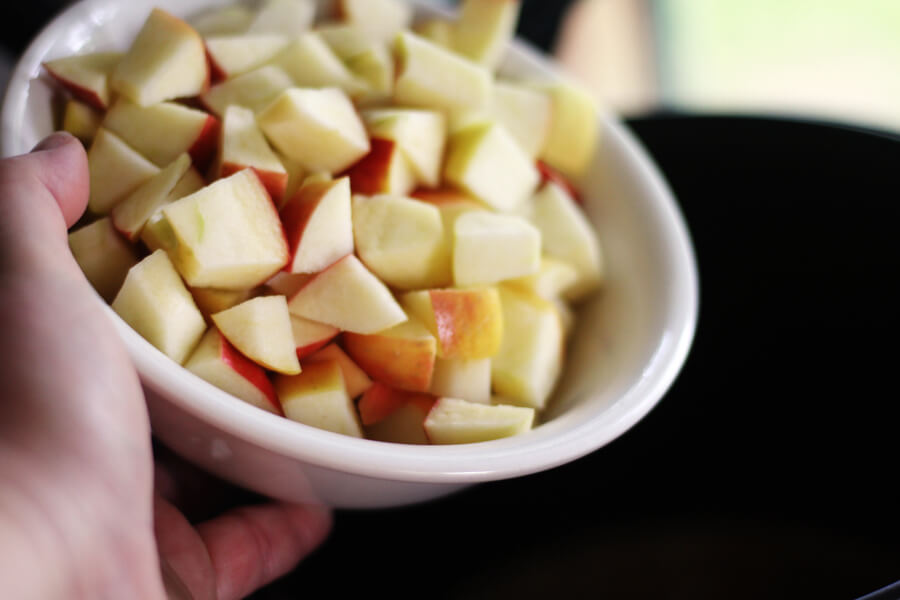 a bowl of fresh, chopped apples being added to a pot