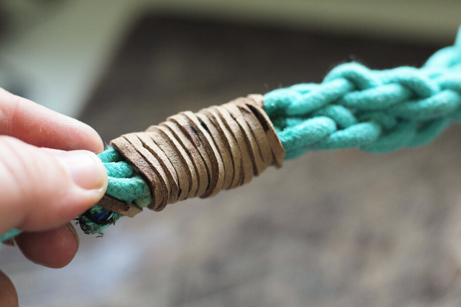 a close up picture of leather cord being wrapped around the glued rope braid to create a hand loop