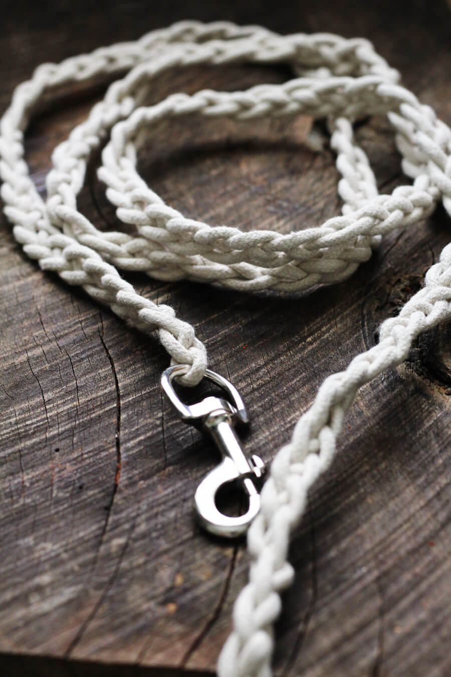 Cotton braided rope dog leash in natural color on a wooden board