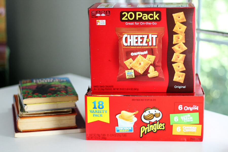 A box of Cheez Its and a box of Pringles on a counter next to a stack of books