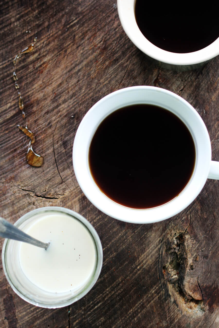 An overhead shot of two cups of coffee on a wooden board, next to a jar of milk and honey drizzle