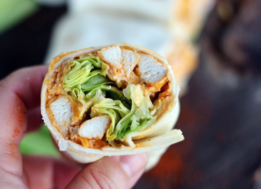 a close up shot of a cut hot chicken wrap, with tender chicken, cheese, hot sauce and crisp lettue