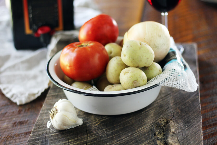 A bowl of petite white potatoes with red tomatoes, next to a bulb of garlic with red wine in the background