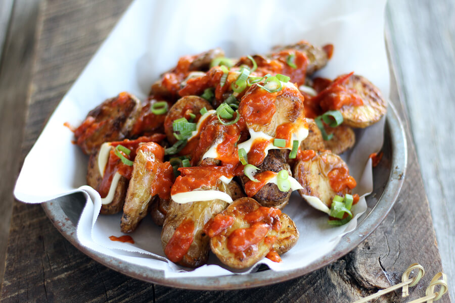 A completed recipe of Patatas Bravas on a plate on a wooden background