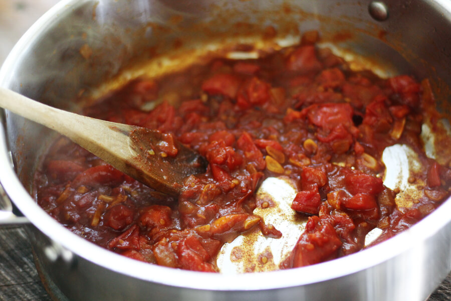 A pan with simmering tomatoes and spices