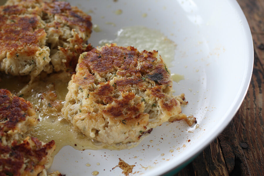 jumbo lump crab cakes being browned in a skillet with butter