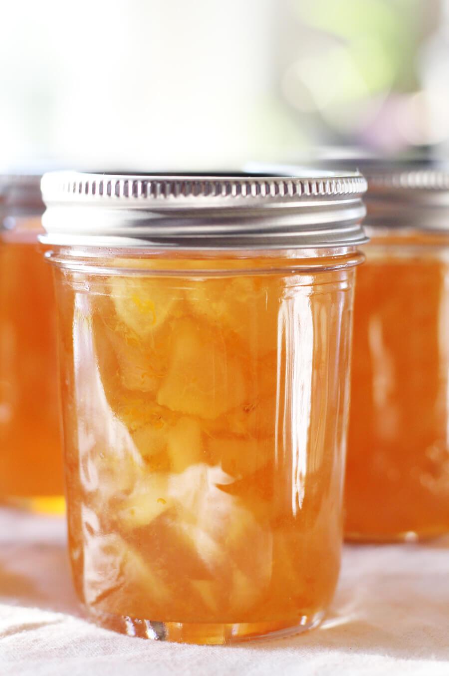 A bright, golden jar of pear preserves.