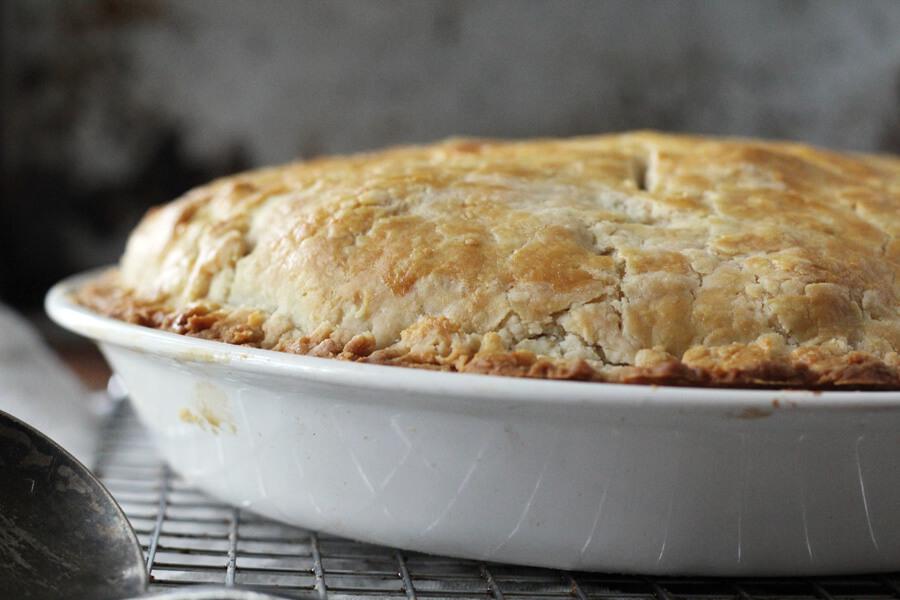 A close up shot of a golden baked chicken pot pie.
