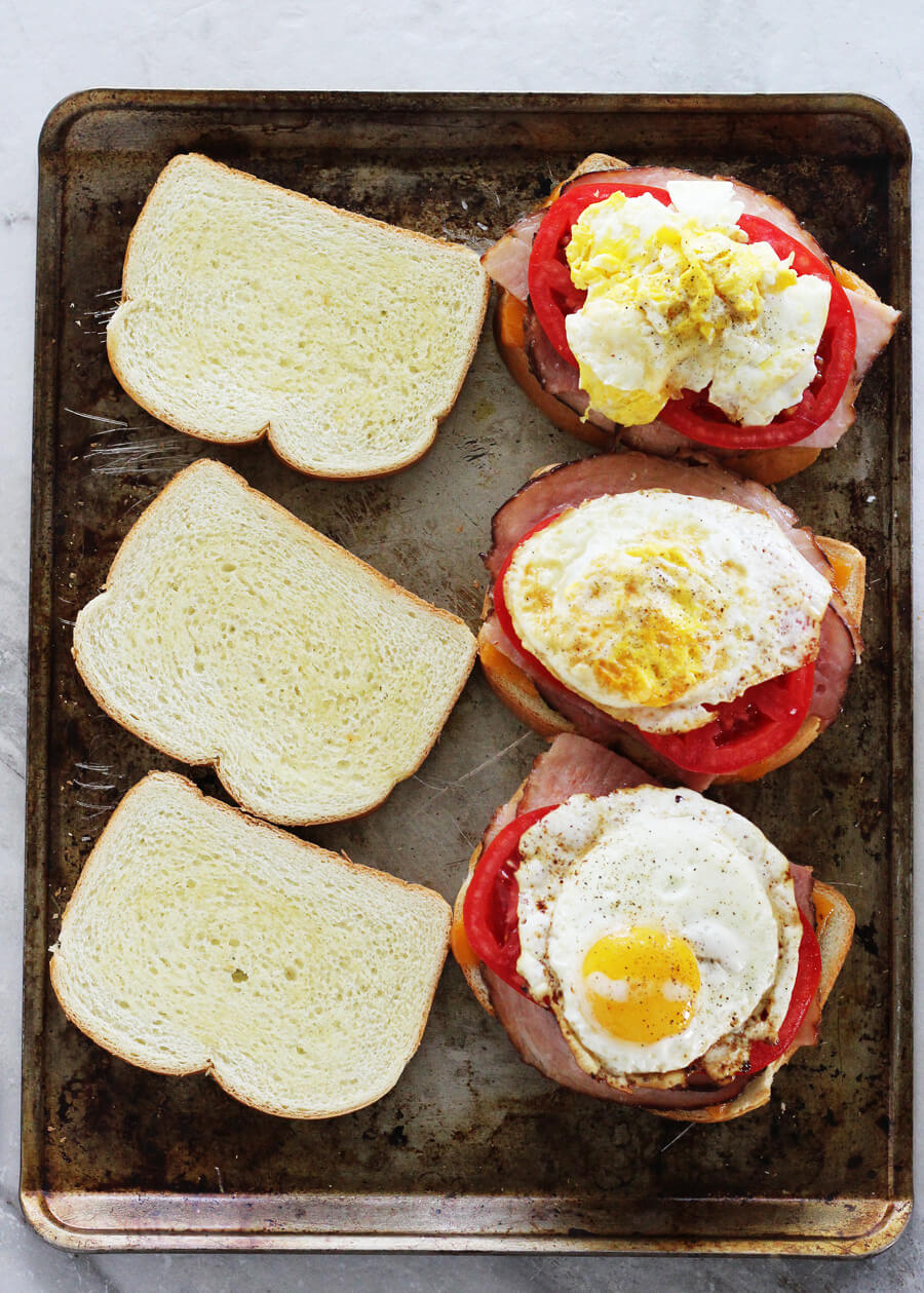toasted white bread topped with layers of cheese, ham, tomato and eggs