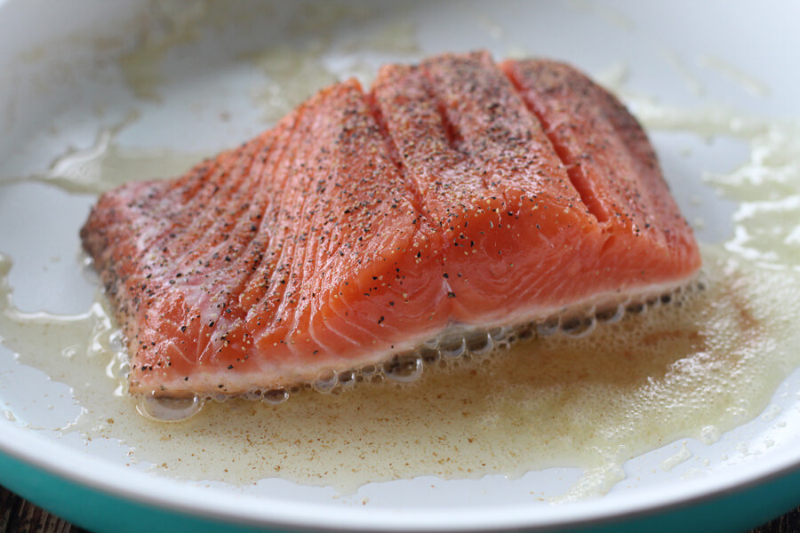 A thick salmon steak searing in butter in a skillet