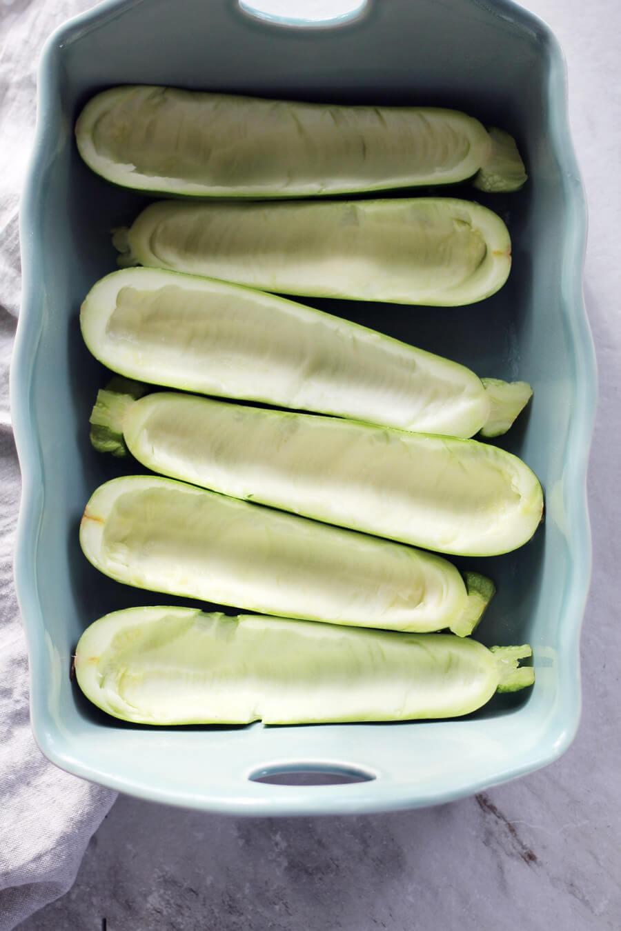 Prepared zucchini halves in a blue baking dish