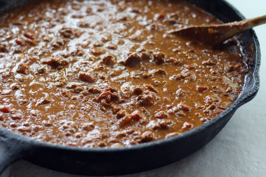 A skillet of cheese, chili, tomatoes and more is the base of this delicious cheese dip recipe.
