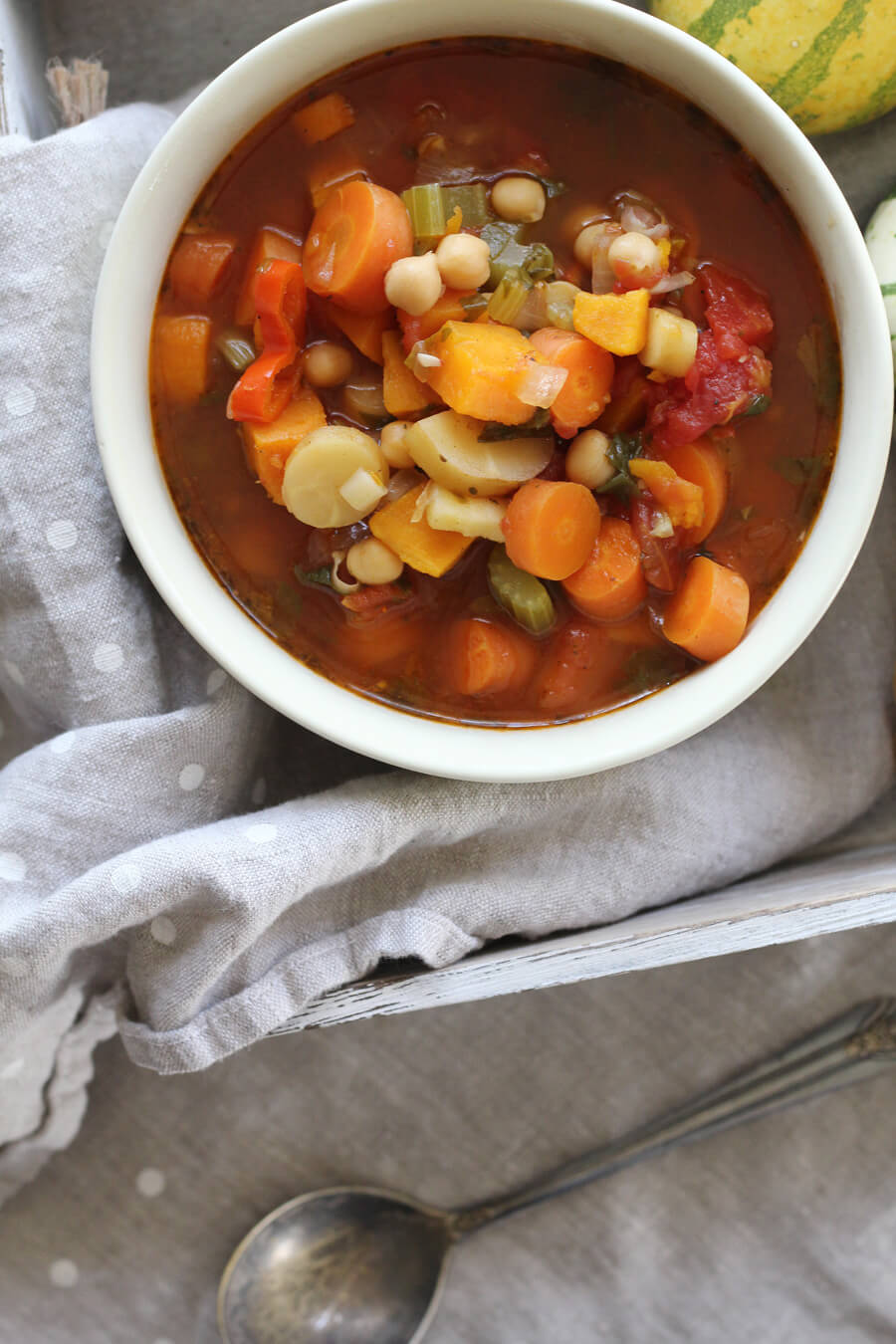 A bowl of homemade vegetable soup with carrots, sweet potatoes, tomatoes, parsnips, celery and more.