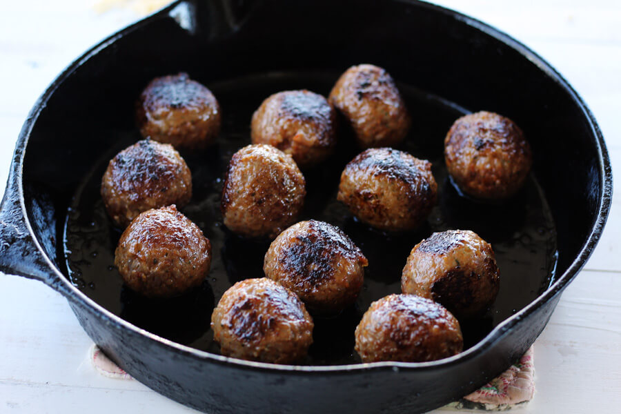 Savory Italian style meatballs browning in a cast iron skillet