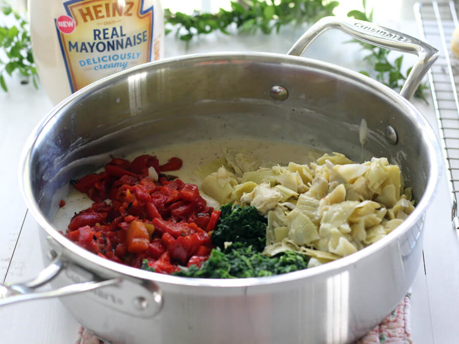 Ingredients in a saucepan, roasted red peppers, spinach, and chopped artichokes