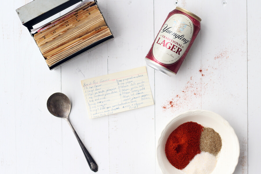 Overhead flat lay shot of recipe box, beer can, spices, vintage spoon, and a hand written recipe card for barbecue sauce