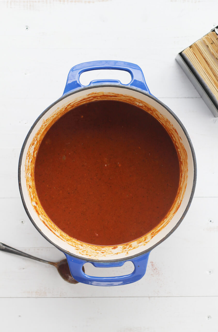 Overhead picture of a blue dutch oven with barbecue sauce