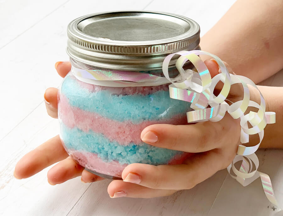 A gift jar of homemade scrub in pink and blue.