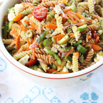 Italian Pasta Salad recipe. Seriously, this is the recipe that my family asks me to make for all of our gatherings. Loaded with colorful veggies and tri-color pasta, this side dish is easy to make ahead. My kids can't stop eating it, either. The best part is how easy it is to make with a few basic tips. And our not-so-secret ingredient. :)