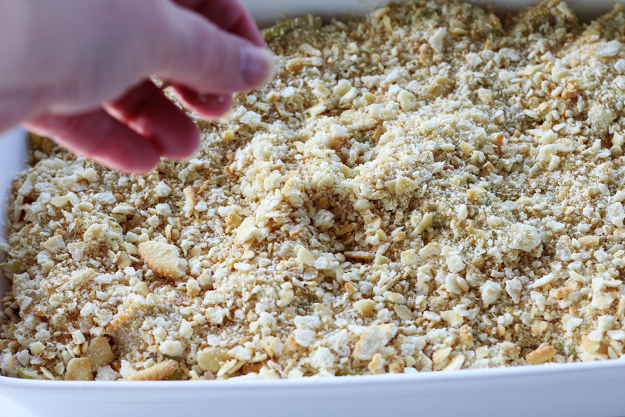 Cracker crumbs being sprinkled on top of a squash casserole