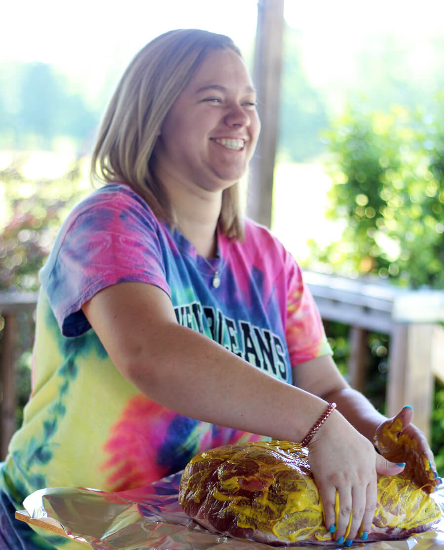 A picture of a young girl, smiling as she prepares a pork roast for the slow cooker.