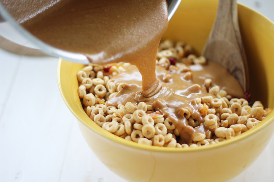 Peanut butter and honey being poured over Cheerios cereal