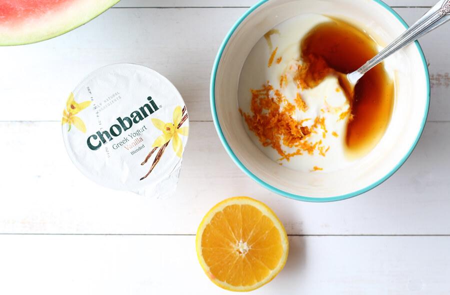 A bowl of yogurt mixed with honey, orange zest, and orange juice.