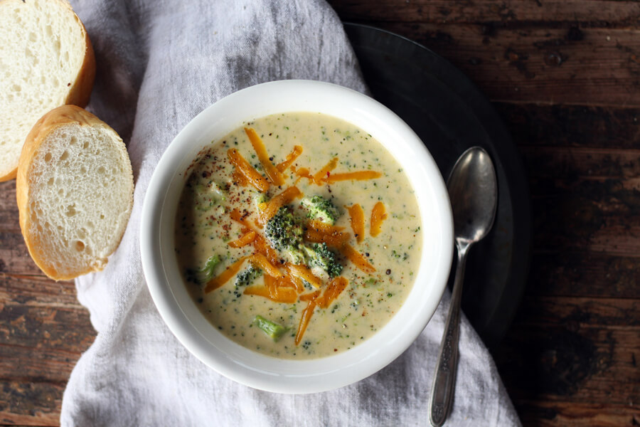 overhead picture of a white bowl filled with soup next to a spoon and french bread
