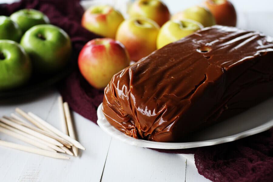 A 5 pound block of gourmet caramel along with an assortment of apple varieties.