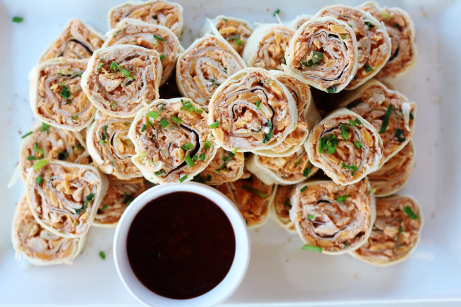 An overhead picture of tortilla roll ups on a white square platter next to a bowl of barbecue sauce