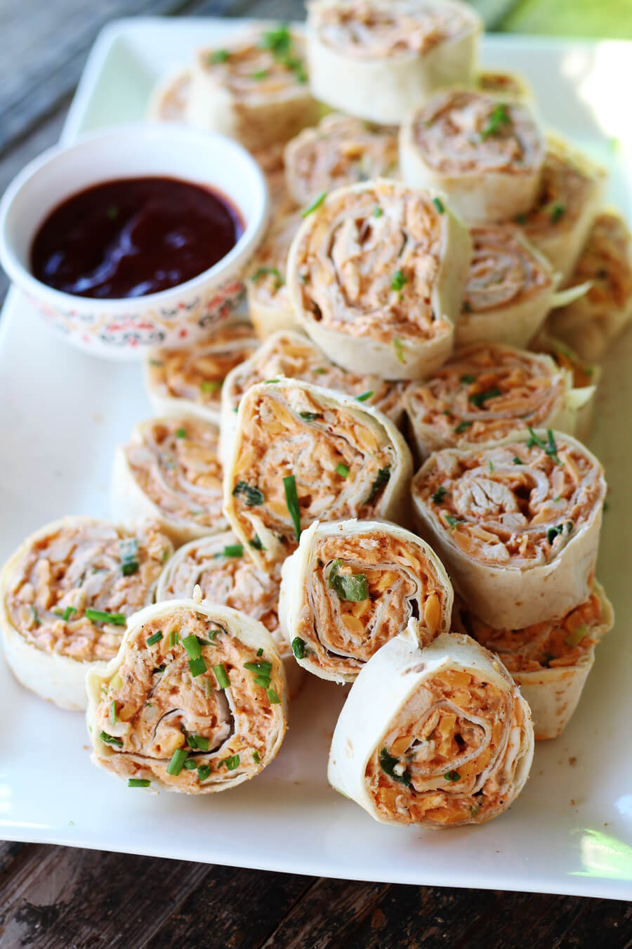A platter of party appetizers with dipping sauce