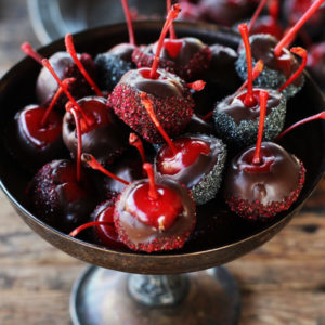 A close up shot of rum spiked maraschino cherries dipped in dark chocolate and dusted with sparkling sugar