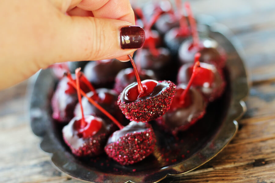 A vintage silver platter with rich, rum-soaked maraschino cherries, dipped in chocolate and sprinkled with sugar glitter
