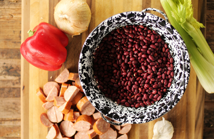 A colander of red beans next to a cutting board with onion, celery, bell pepper and smoked sausage