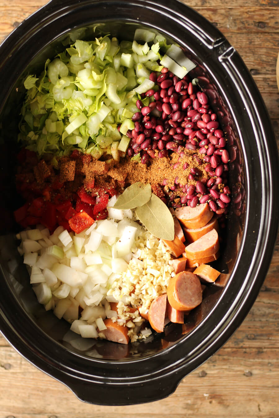 Overhead picture of a pot filled with ingredients to make red beans and rice, including garlic, onions, smoked sausage, peppers, celery, and more.