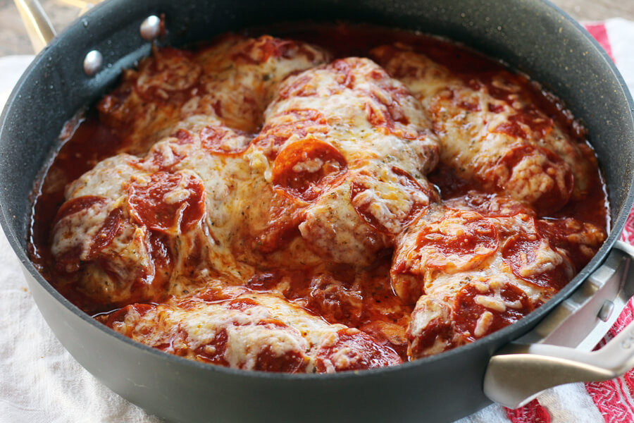 Front view of a skillet filled with saucy chicken cutlets topped with cheese and pepperoni