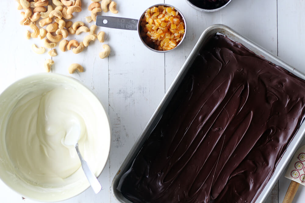 a pan of dark chocolate next to a bowl of melted white chocolate, plus roasted cashews and orange peel
