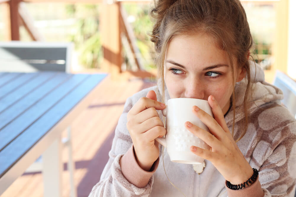 a young woman drinking from a coffee mug