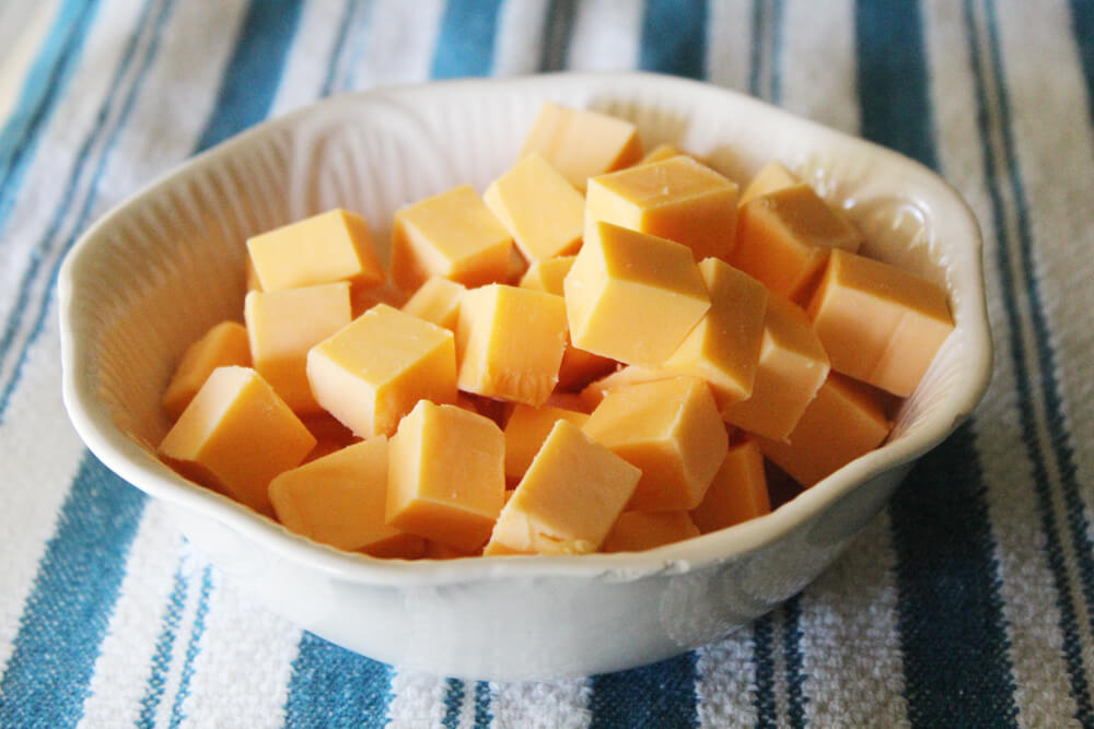 a white bowl filled with cubes of cheddar cheese