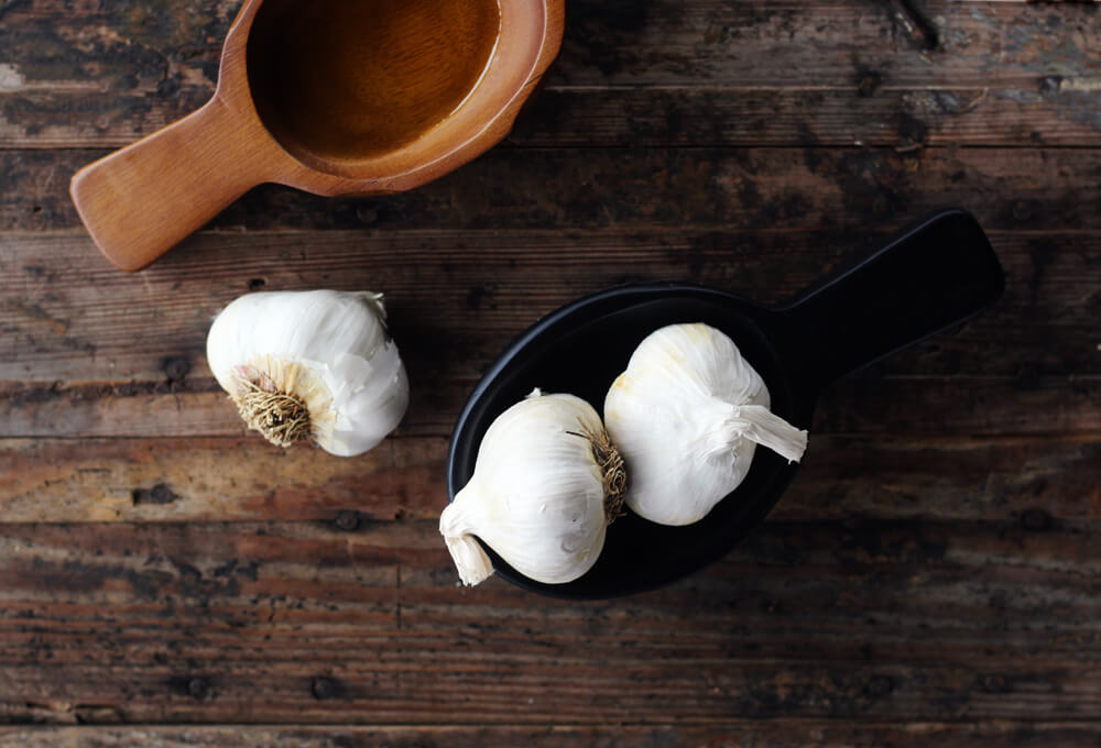 overhead picture of garlic on a wooden board