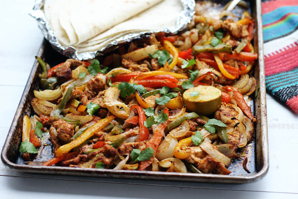 a pan of spiced chicken, onions, and bell peppers