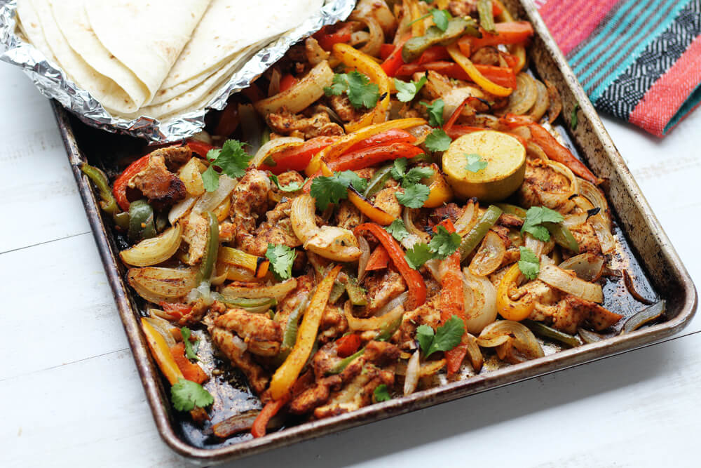 a sheet pan with roasted bell peppers and seasoned chicken