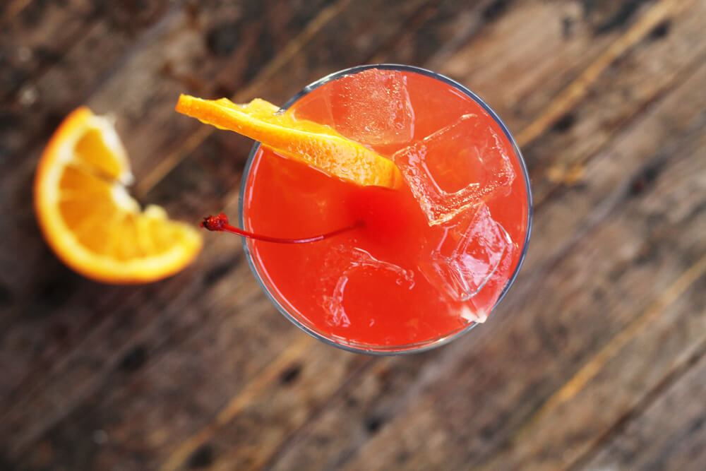 overhead picture of a cocktail served in a hurricane glass with a wedge of orange and a maraschino cherry