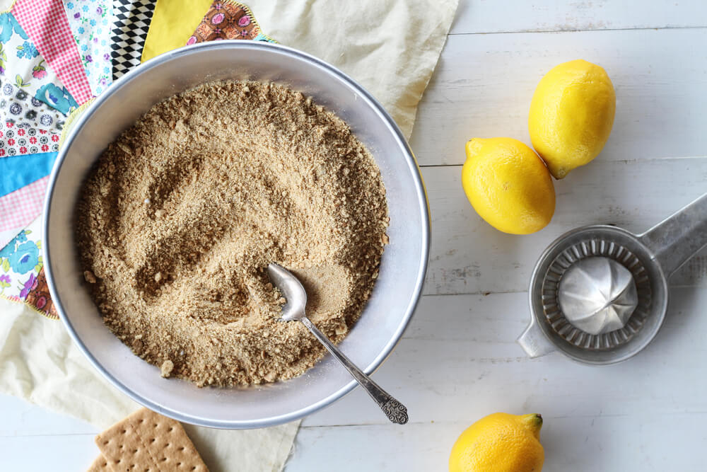 graham cracker crumbs in a metal pie next to fresh lemons