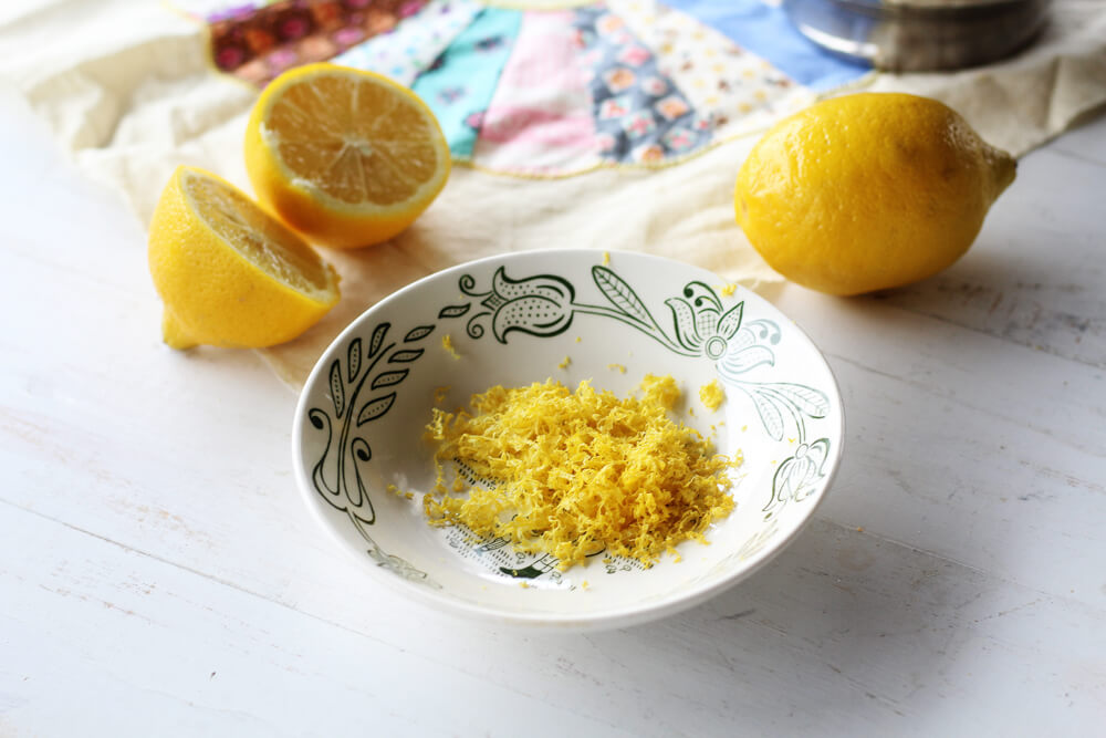 a bowl of lemon zest with lemons in the background