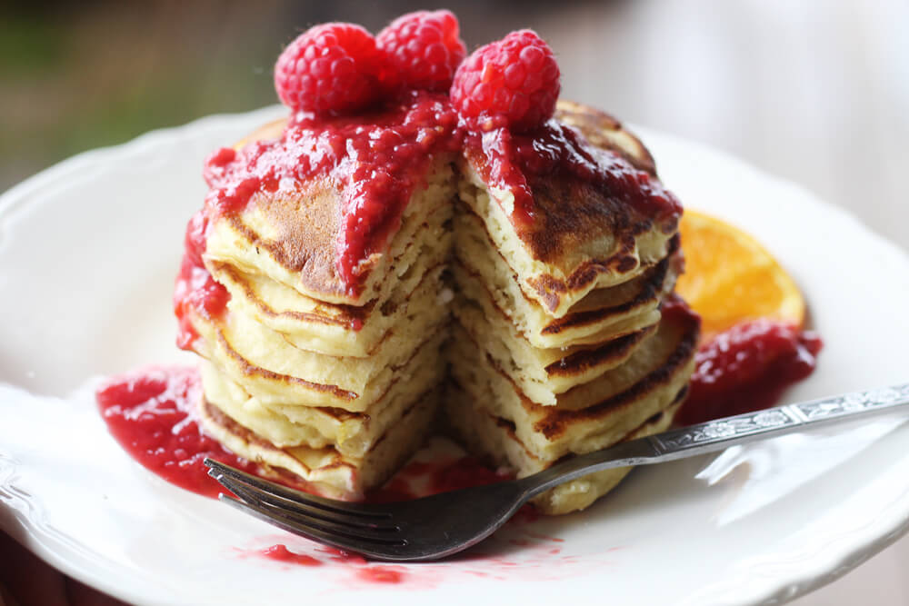a close up picture of a stack of pancakes on a white plate