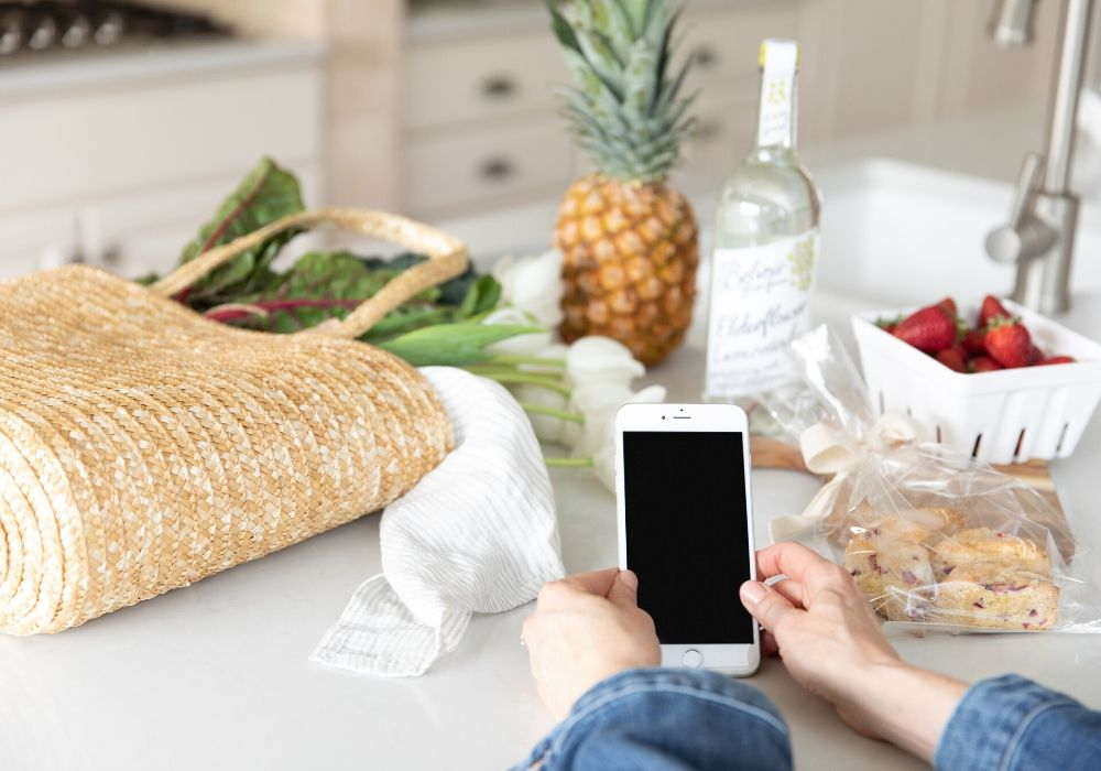 a counter with groceries and a woman holding a smart phone