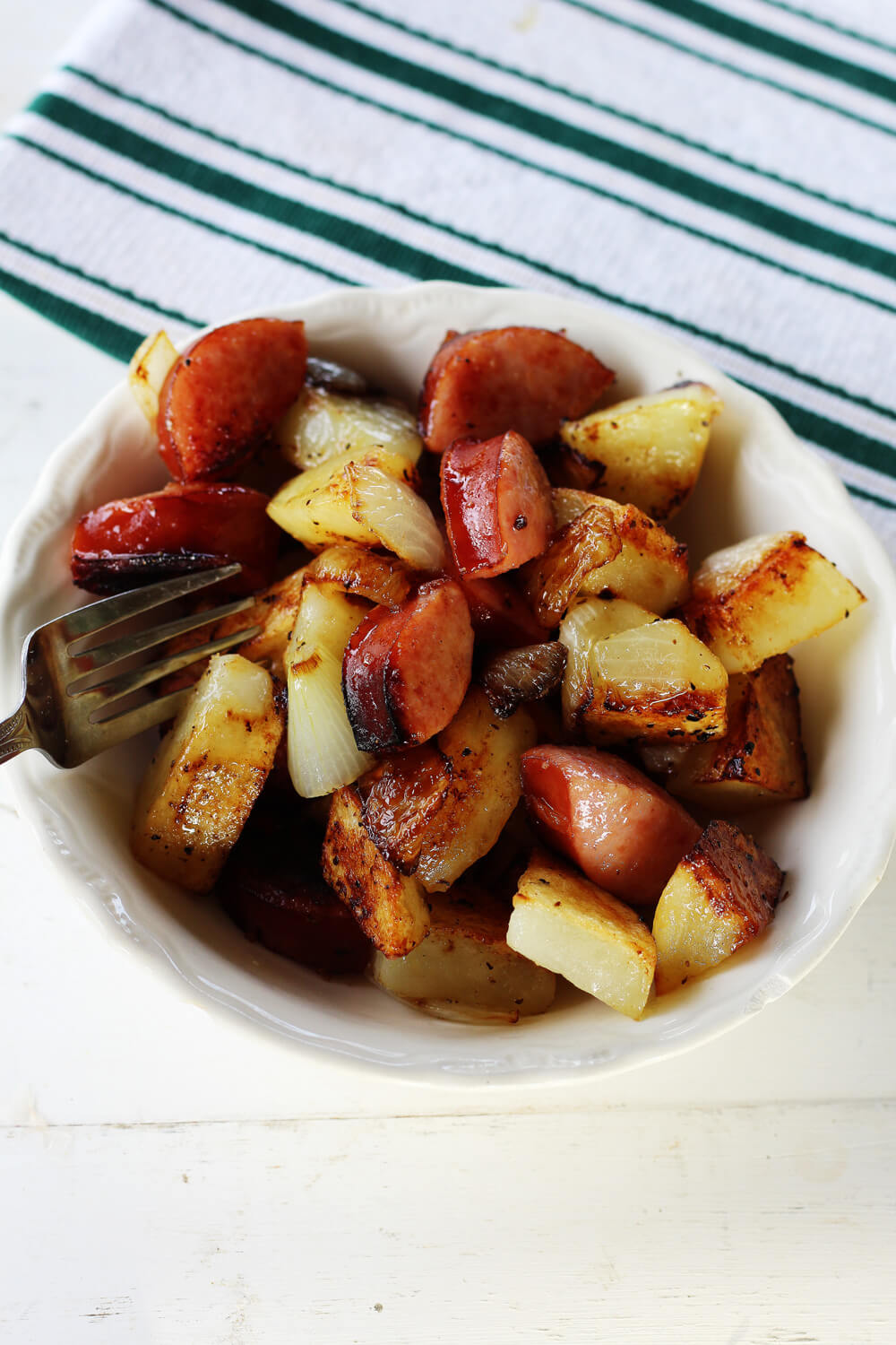 a white bowl with potatoes onions and sasuage