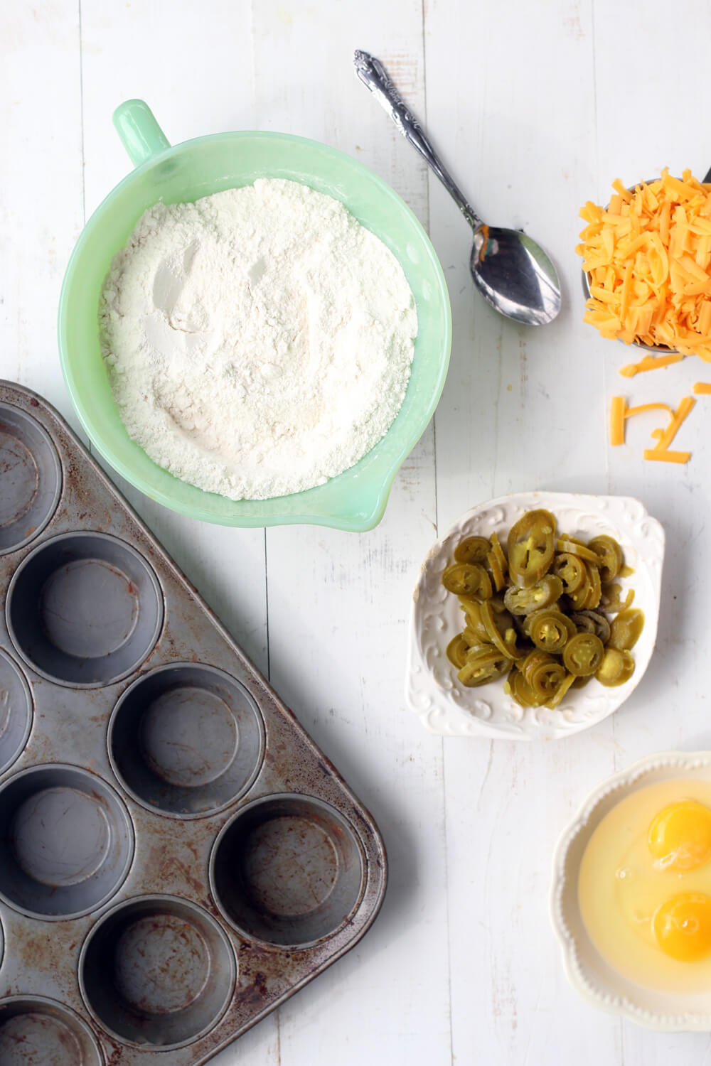 ingredients on a white board including cornmeal, flour, shredded cheese, jalapeno peppers, and eggs