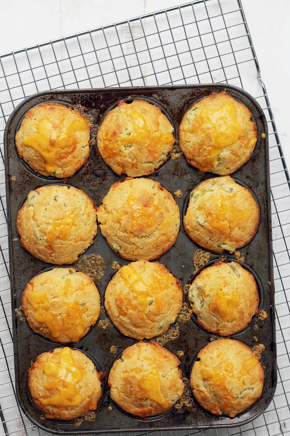 Overhead picture of a muffin tin cooling on a wire rack.
